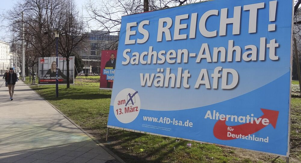 A man walks past a campaign poster of right-populist AfD party reading It's enough - Saxony-Anhalt elects AfD in Magdeburg, Germany.