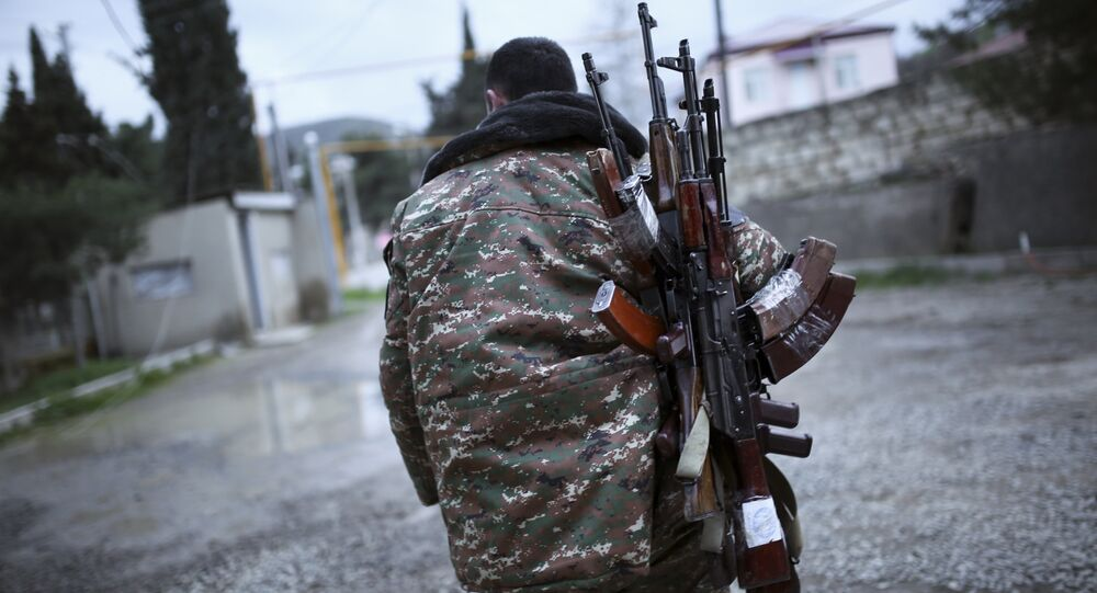 An ethnic Armenian fighter carries Kalashnikov machine guns to his comrade-in-arms at Martakert province in the separatist region of Nagorno-Karabakh, Azerbaijan, Monday, April 4, 2016