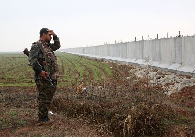 A Kurdish People's Protection Unit(YPG) fighter stands near a wall which activists say was put up by Turkish authorities, on the Syria-Turkey border in the western Syrian countryside of Ras al-Ain on February 2, 2016