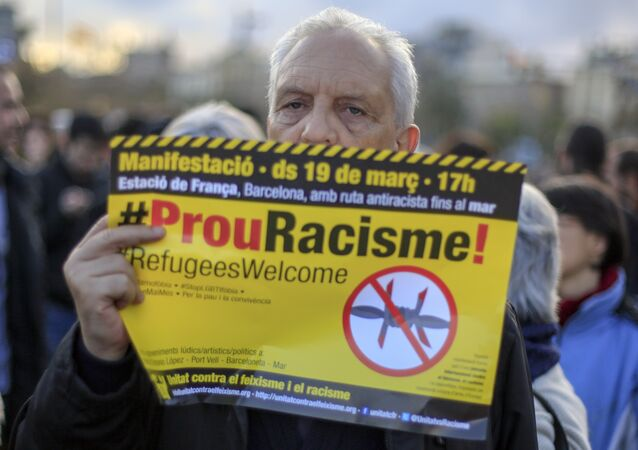 "A protester called by Stop Mare Mortum and ""Unity against Fascism and Racism"" platforms, holds a poster reading Stop Racism in Catalan during the European March for Refugee Rights in Barcelona on March 19, 2016."