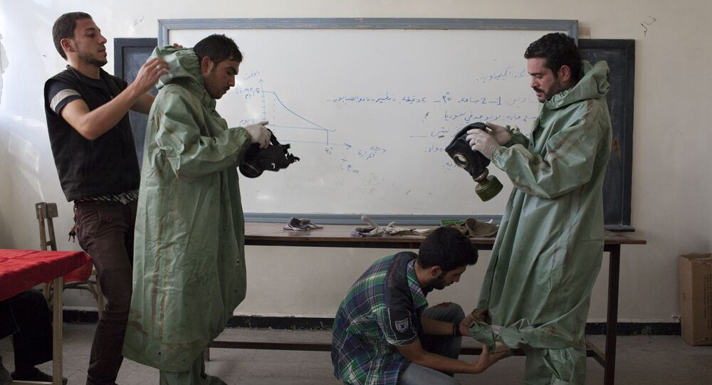 Aleppo University student, shows Syrian citizens hows to put protective gear as he instructs them with rudimentary means of how to respond to a chemical attack, in the northern Syrian city of Aleppo (File)