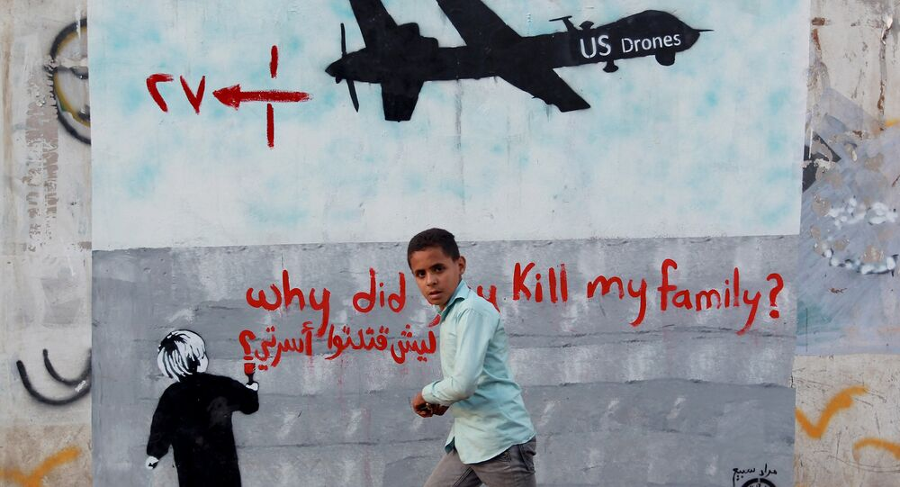 A Yemeni boy (C) walks past a mural depicting a US drone and reading  Why did you kill my family on December 13, 2013 in the capital Sanaa.