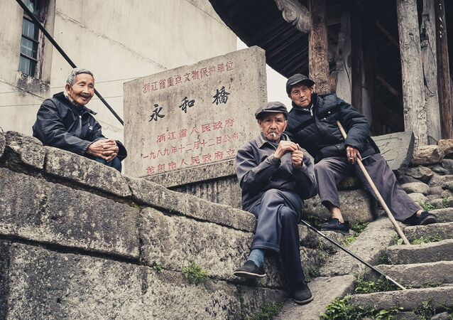 Old men hanging out at the entrance to covered wooden bridge built in the Ming Dynasty in a small town in Zhejiang Province, China