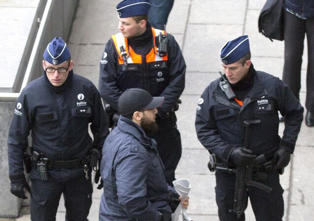 Accused Bilal El Makhoukhi, center front, speaks with police outside the main courthouse in Antwerp, Belgium