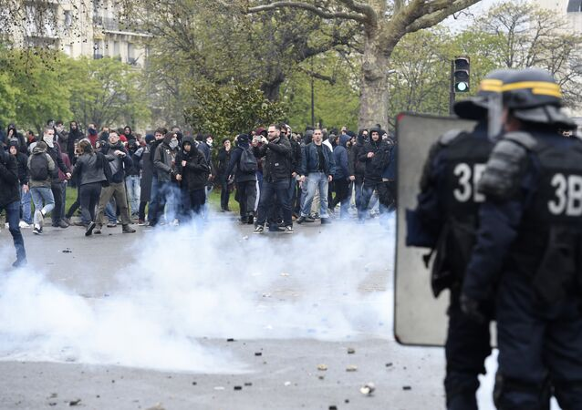 Protesters face anti riot policemen during clashes as part of a demonstration on April 9, 2016 in Paris, against the French government's proposed labour law reforms