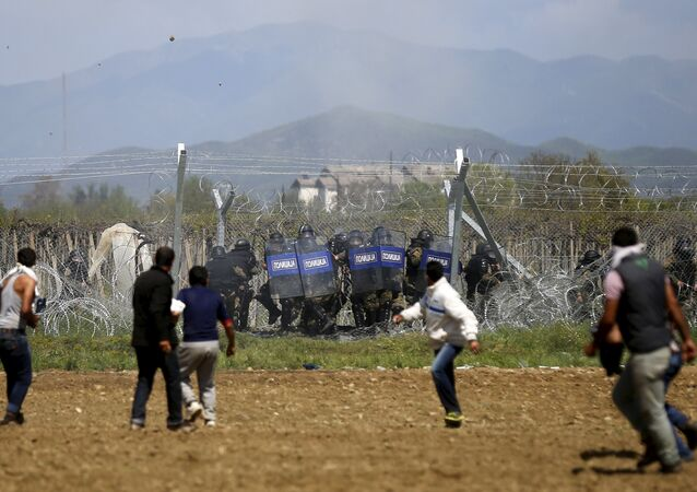 Migrants throw stones at Macedonian police during clashes next to a border fence at a makeshift camp at the Greek-Macedonian border near the village of Idomeni, Greece