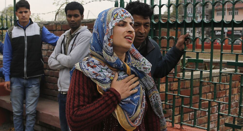 A Kashmiri woman reacts as people stand on a pavement following tremors in Srinagar, Indian controlled Kashmir