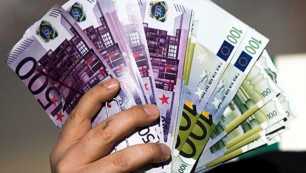 An activist shows fake banknotes during a demonstration outside the European Commission (EC) headquarters. - Sputnik International