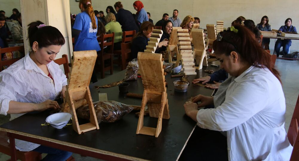 Syrian employees work at the production of Syria's first locally made cigars at a factory in the northeastern province of Latakia