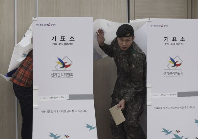 A South Korean army soldier comes out of a booth to cast his preliminary vote for the upcoming parliamentary election at a local polling station in Seoul.