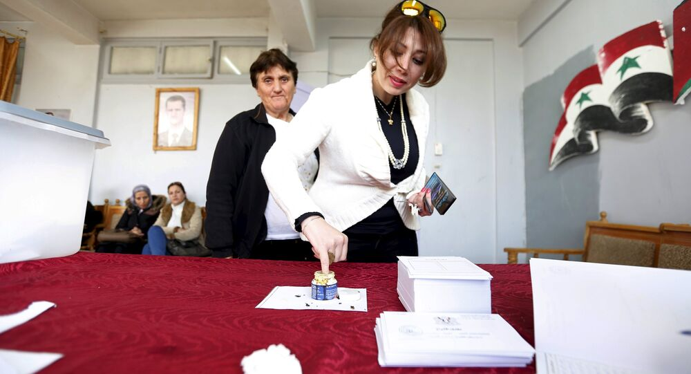A woman inks her finger after casting her vote at a polling station during the parliamentary elections in Damascus, Syria
