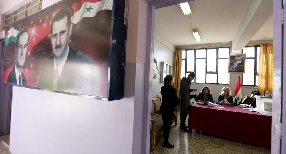 A banner showing Syria's president Bashar al-Assad and his father, former president Hafez al-Assad is seen inside a polling station during the parliamentary elections in Damascus, Syria