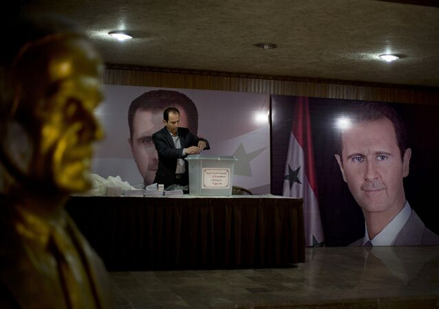 A Syrian election official waits for voters at a polling station with posters of President Bashar Assad during the parliamentary election in Damascus, Syria