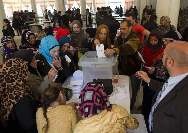 A Syrian woman casts her vote at a polling station during the Syrian parliamentary election in Damascus, Syria