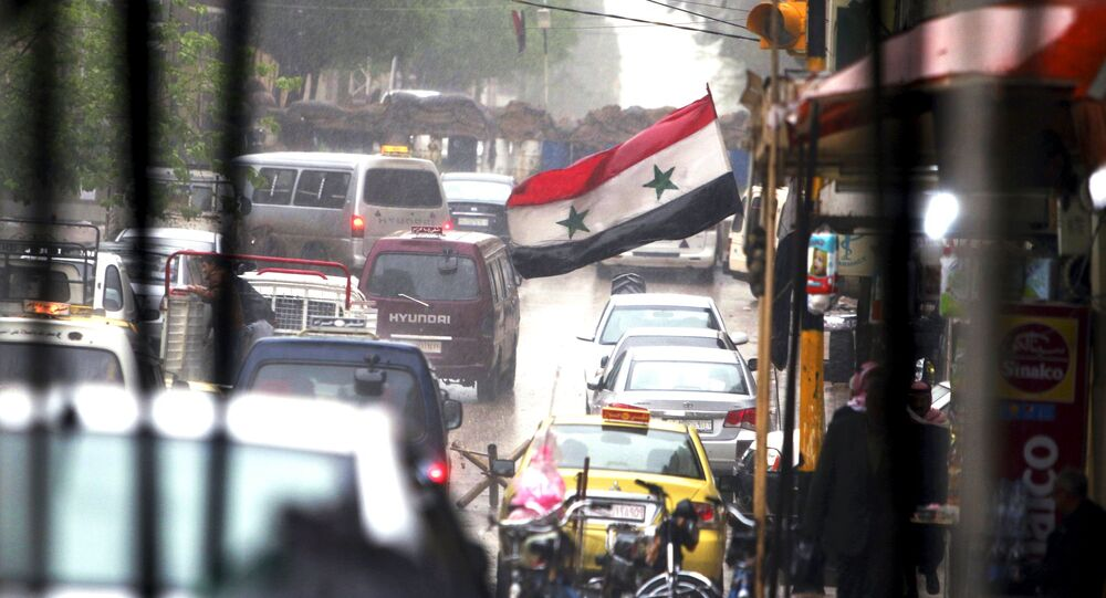 Vehicles travel on a busy road near a Syrian national flag in Qamishli, Syria April 11, 2016.