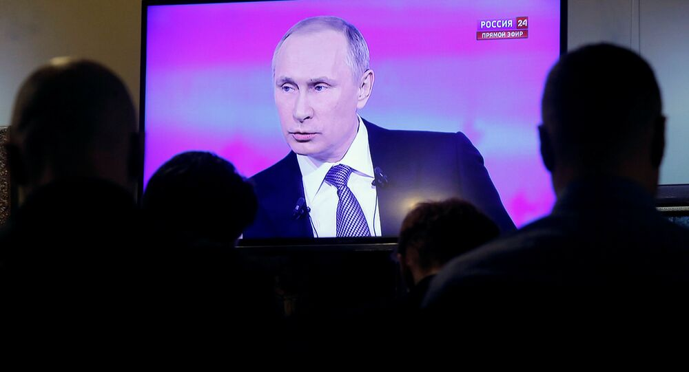Journalists watch a live broadcast on an electronic screen showing nationwide call-in attended by Russian President Vladimir Putin in Moscow, Russia, April 14, 2016