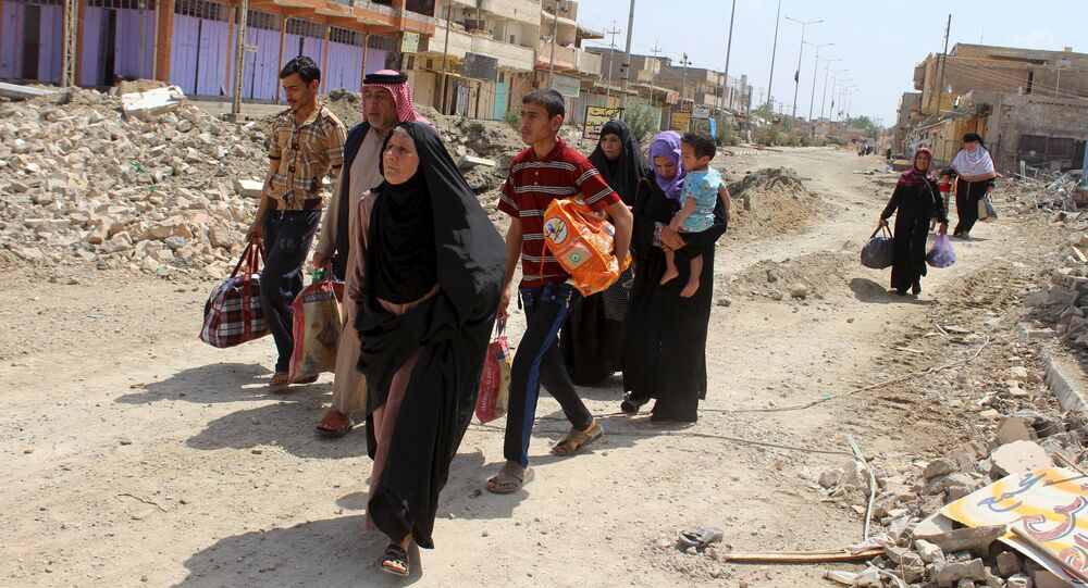 Civilians flee their homes to head to safer areas due to clashes between Iraqi security forces and Islamic State militants in the town of Hit in Anbar province, Iraq April 12, 2016