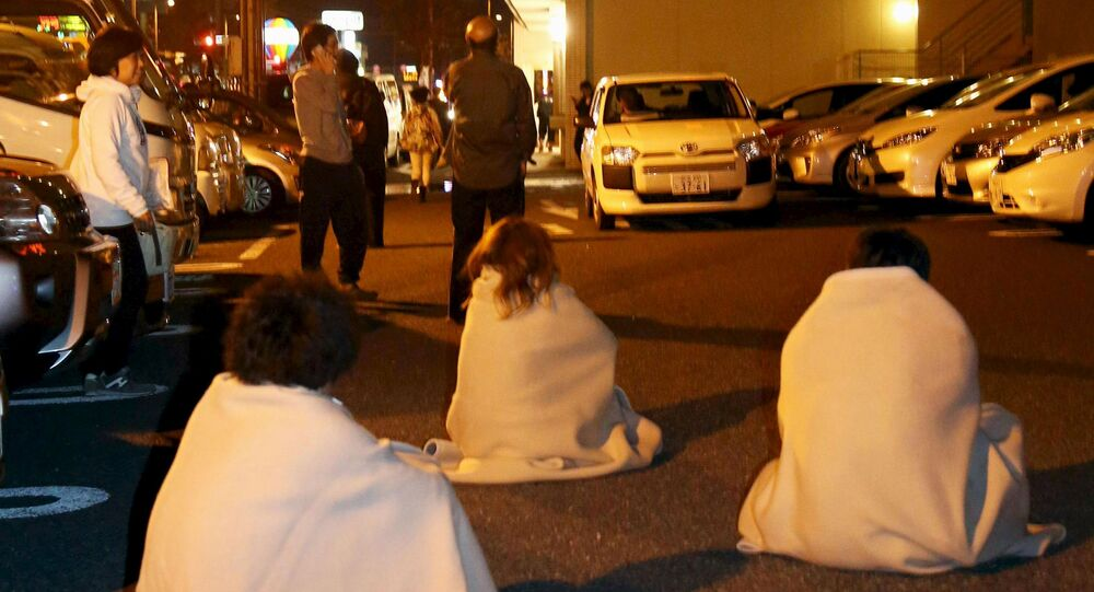People wrapped in blankets sit on the road as they are evacuated from a hotel after an earthquake in Kumamoto, southern Japan, in this photo taken by Kyodo April 14, 2016