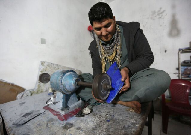 In this Monday, March 28, 2016 photo, an Afghan man works at a lapis lazuli factory in the city of Kabul, Afghanistan.