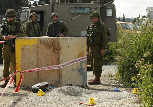 An axe is seen on the ground as Israeli soldiers stand guard at the site where a Palestinian man, armed with an axe, reportedly attacked an Israeli soldier at the entrance of al-Arroub Palestinian refugee camp, between Hebron and Bethlehem on April 14, 2016