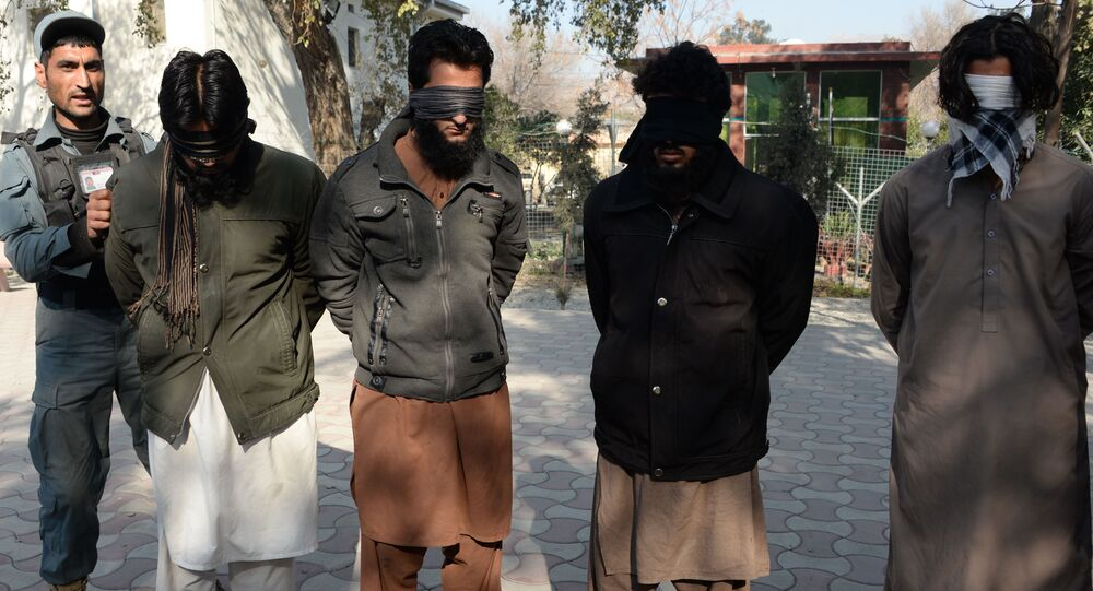 Alleged fighters for Islamic State (IS) stand handcuffed while being presented to the media at a police headquarter in Jalalabad (File)