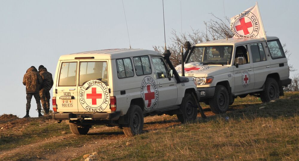 Vehicles of the representatives of the International Committee of the Red Cross on the demarcation line where a search is being conducted for the bodies of the victims