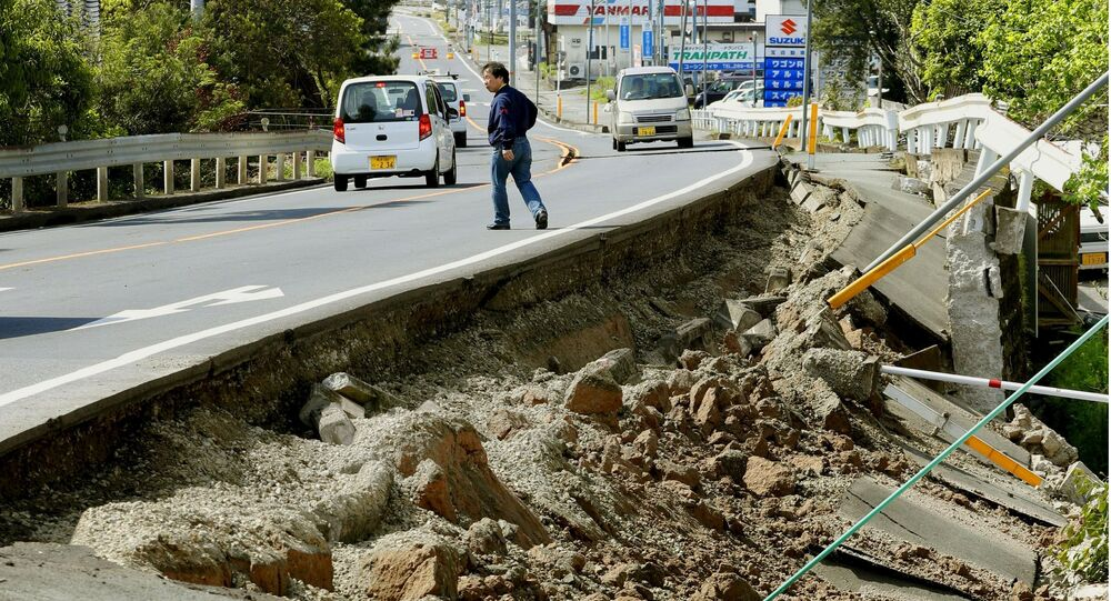 A man walks near a damaged road caused by an earthquake in Mashiki town, Kumamoto prefecture, southern Japan, in this photo taken by Kyodo April 15, 2016