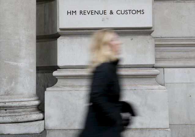 A pedestrian walks past the headquarters of Her Majesty's Revenue and Customs (HMRC) in central London, Britain in this February 13, 2015 file photo
