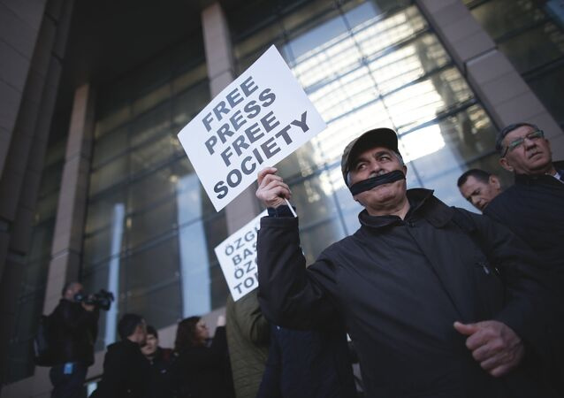 Turkish journalists cover their mouths with black ribbons before the trial of Can Dundar, the editor-in-chief of opposition newspaper Cumhuriyet and Erdem Gul, the paper's Ankara representative, outside the courthouse in Istanbul, Friday, April 1, 2016