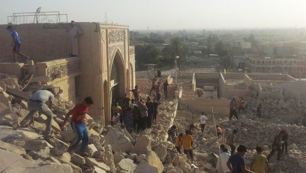 People walk on the rubble of the destroyed Mosque of The Prophet Younis, or Jonah, in Mosul, 225 miles (360 kilometers) northwest of Baghdad, Iraq (File) - Sputnik International