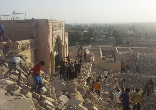 People walk on the rubble of the destroyed Mosque of The Prophet Younis, or Jonah, in Mosul, 225 miles (360 kilometers) northwest of Baghdad, Iraq (File)