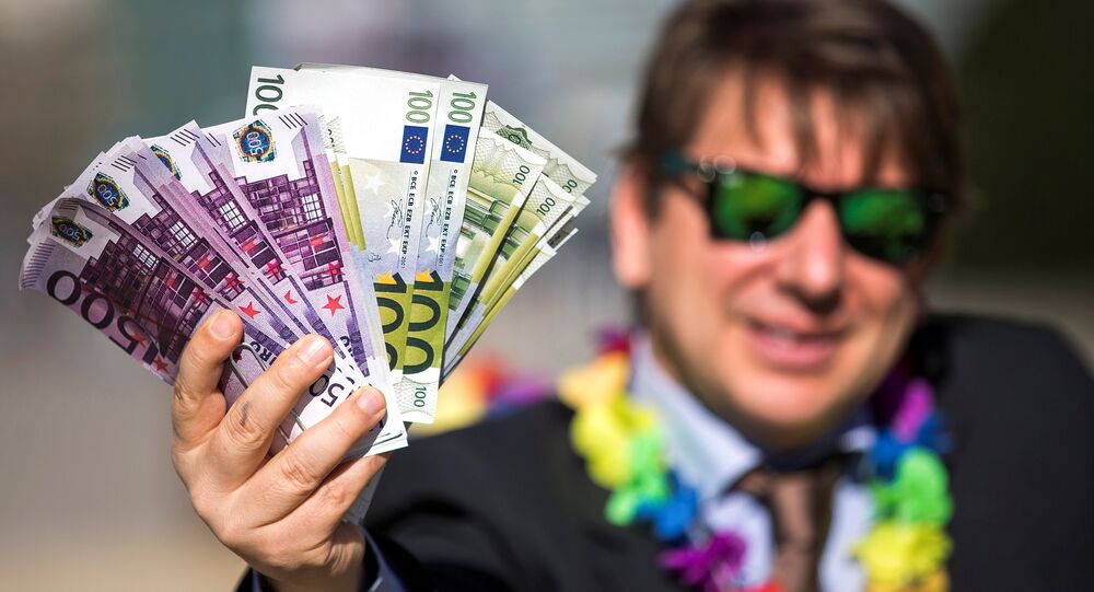 An activist shows fake banknotes during a demonstration outside the European Commission (EC)