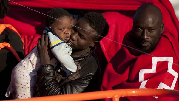 A migrants wrapped in a red cross blanket holds a child on arrival into the southern Spanish port of Malaga on January 27, 2016 after an inflatable boat carrying 55 Africans, seven of them women and six chidren, was rescued by the Spanish coast guard off the Spanish coast (File) - Sputnik International