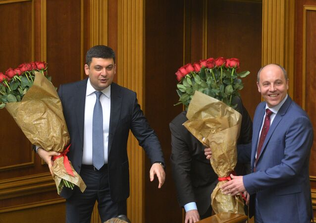Newly appointed Prime Minister of Ukraine Volodymyr Groysman (L) and Andriy Parubiy, newly appointment chair of the Ukrainian Parliament, hold bouquets of red roses during a parliamentary session in Kiev on April 14, 2016