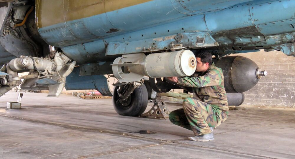 A Syrian Army soldier attaches a missile to a jet at Dmeir military airport, 50 km north-east of Damascus, on April 8, 2016