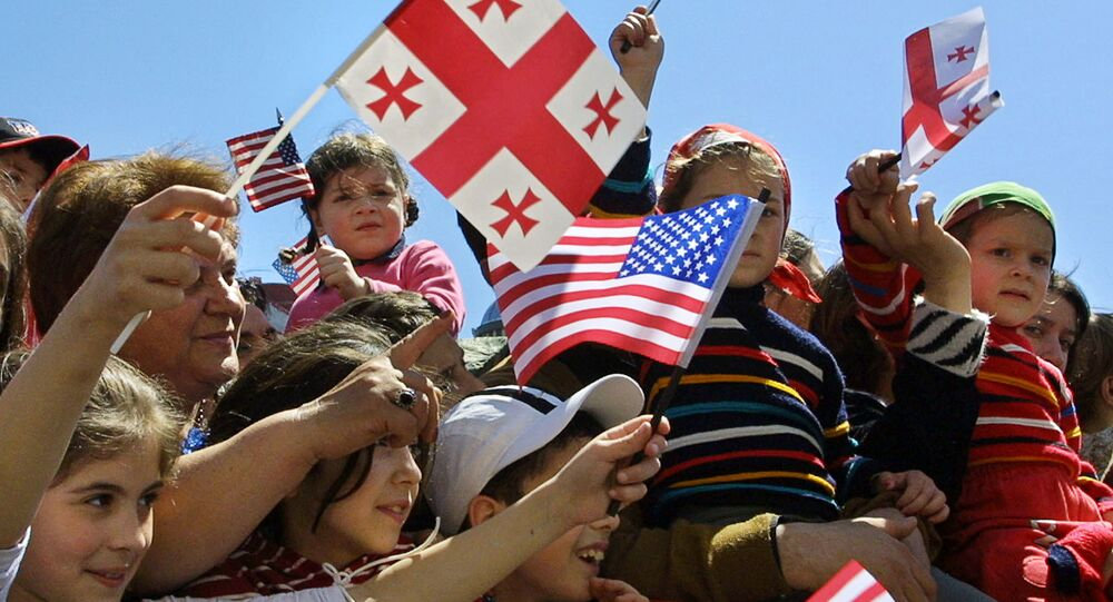 Children wave Georgian and US flags at Freedom Square in the Georgian capital Tbilisi (File)