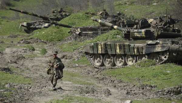 A soldier of the defense army of Nagorny Karabakh walks past tanks at a field position outside the village of Mataghis, some 70km north of Karabakh's capital Stepanakert, on April 6, 2016 - Sputnik International