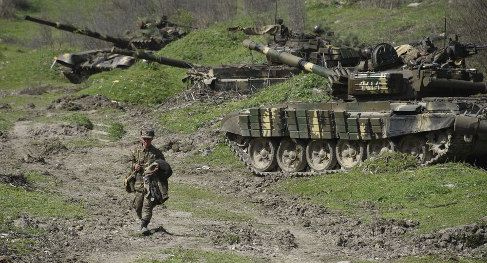A soldier of the defense army of Nagorny Karabakh walks past tanks at a field position outside the village of Mataghis, some 70km north of Karabakh's capital Stepanakert, on April 6, 2016