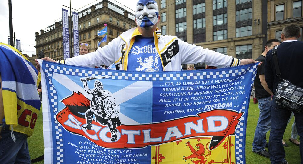 A pro Independence supporter wearing a Guy Fawkes mask bearing St Andrew's Cross holds a flag during a rally in George Square in Glasgow, Scotland (File)