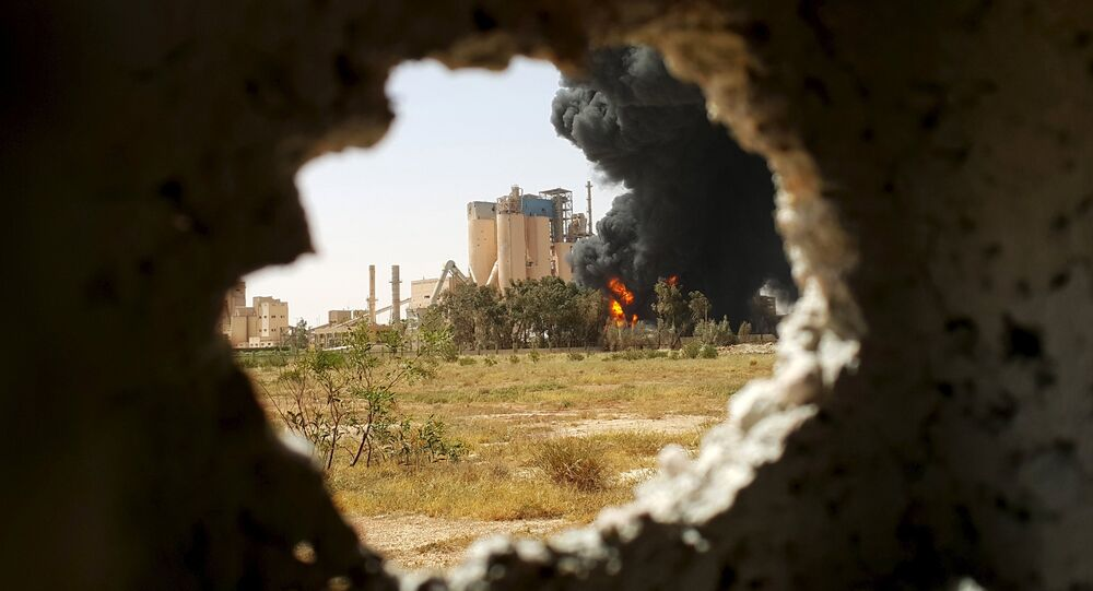 A fire is seen next to the Libyan cement factory