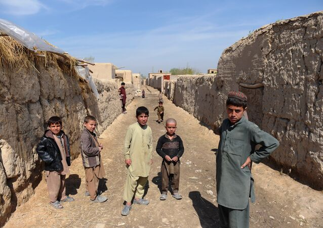 Afghan children watch Afghan National Army (ANA) soldiers in Dand-e-Ghori district in Baghlan province on March 15, 2016.