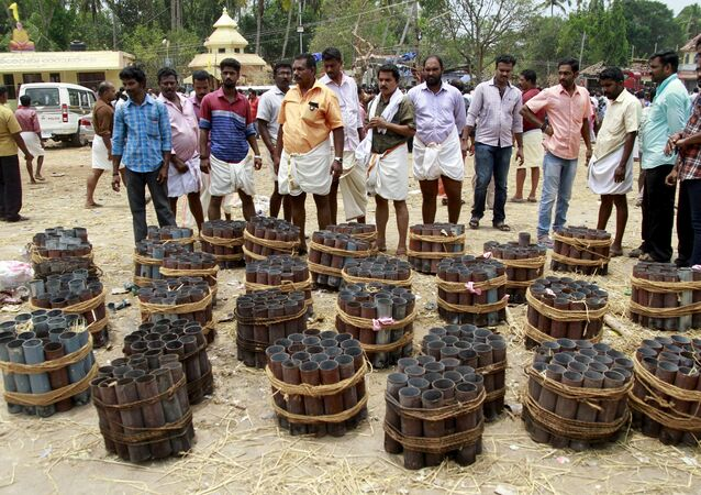People stand next to empty fire cracker shells inside the compound of a temple after a fire broke out at the temple in Kollam in the southern state of Kerala, India, April 10, 2016.