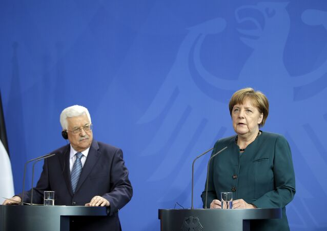 German Chancellor Angela Merkel, right, and Palestinian President Mahmoud Abbas, left, address the media during a joint news conference as part of a meeting at the chancellery in Berlin, Germany, Tuesday, April 19, 2016.