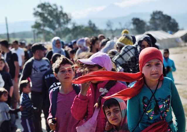 Refugees and migrants queue for food at the makeshift camp along the Greek-Macedonian border near the village of Idomeni on April 20, 2016.