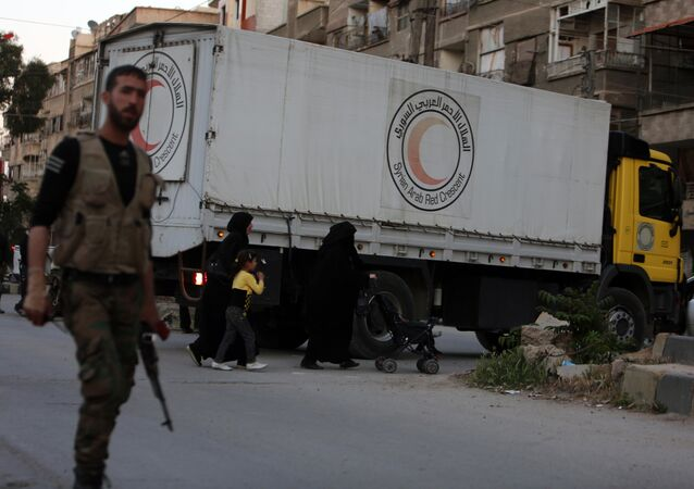 Syrian Aarb Red Crescent trucks transporting aid arrive in Ain Tarma, in the eastern Ghouta area, a rebel stronghold east of the Syrian capital Damascus