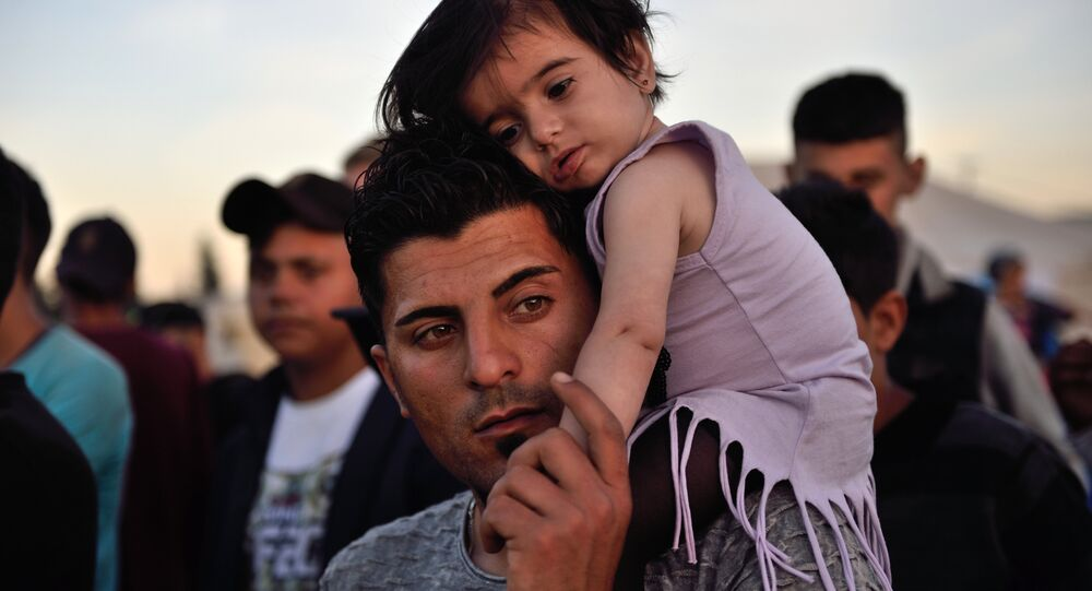 A man carries a child on his shoulders at the migrant and refugee makeshift camp near the village of Idomeni on the Greek-Macedonian border on April 16, 2016.