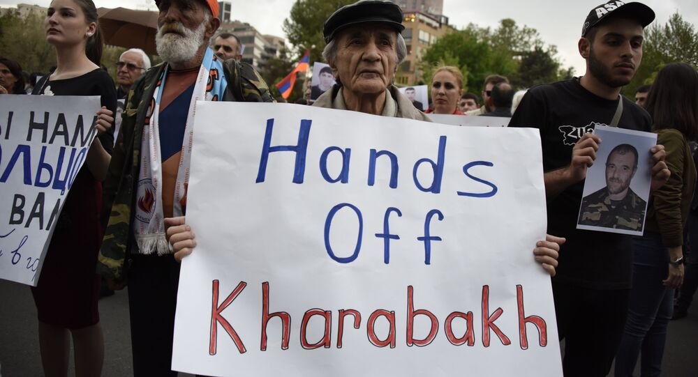 An Armenian man holds a placard reading Hands off Karabakh as he takes part in a rally in Yerevan on April 21, 2016.