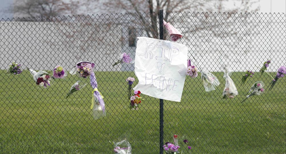 Flowers and a sign appear on the fence at Paisley Park Studios, the home and studio of singer Prince, Thursday, April 21, 2016 in Chanhassen, Minn. Prince died at the home, Thursday, at the age of 57.
