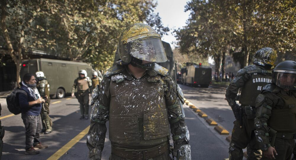 Riot police officers stands on the street after protesting students pelted them with paint during a protest demanding that the government make true its promise of free education, in Santiago, Chile, Thursday, April 21, 2016.