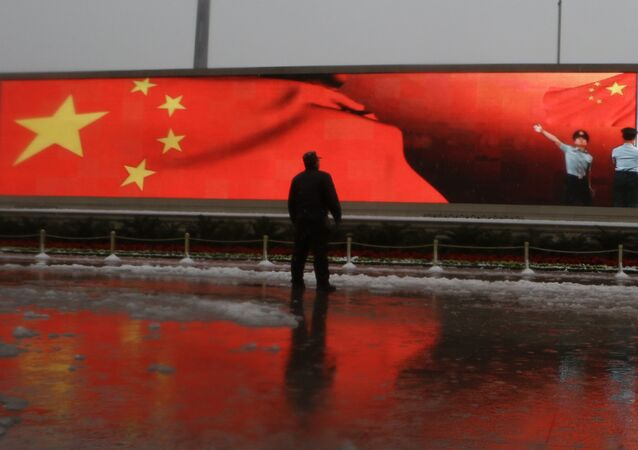 Chinese man stands near a screen displaying the Chinese national flag (File)